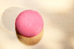 Traditional french pink macaron with sun shadows on wooden background Royalty Free Stock Photography