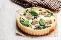 Traditional  french quiche pie  with spinach and mushroom on wood Royalty Free Stock Image