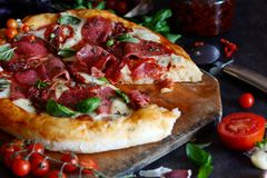Traditional Fresh Italian pizza with dried salami tomatoes mozzarella cherry tomatoes and fresh green basil leaves. stock photos