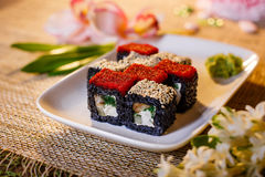 Traditional fresh japanese sushi rolls on a black background. Black roll with eel and caviar on a white plate Royalty Free Stock Photography