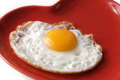 Traditional fried egg on heart shape plate. Traditional fried egg on red heart shape plate royalty free stock photo