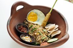 Traditional fried rice with satay chilly sauce,tomato and pickle. Traditional fried rice with egg, satay, chilly sauce tomato and pickle in a brown bowl with royalty free stock photography