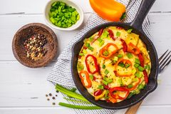 Traditional fritatta with peppers and potatoes in a cast iron pan. White wooden background