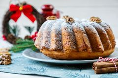 Traditional fruitcake for Christmas decorated with powdered sugar and nuts, raisins and cup of coffee or tea. stock photo