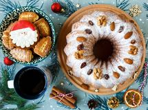 Traditional fruitcake for Christmas decorated with powdered sugar and nuts, raisins and cup of coffee or tea. stock image