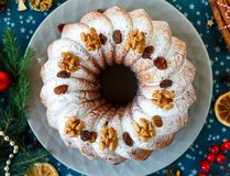Traditional fruitcake for Christmas decorated with powdered sugar and nuts, raisins. Delicioius Homemade Pastry. New year royalty free stock photos