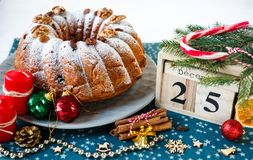 Traditional fruitcake for Christmas decorated with powdered sugar and nuts, raisins next to wooden calendar with date 25 december stock photography