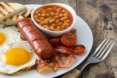 Traditional full English breakfast with fried eggs, sausages, beans, mushrooms, grilled tomatoes and bacon Stock Photography