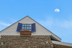 Traditional gable house with moon sky. Traditional gable house with glass window stone cladding and flower bed under moon sky Royalty Free Stock Images