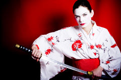 Traditional Geisha with sword. A view of a woman in traditional white Japanese Geisha makeup and kimono, unsheathing a long sword or katana, sometimes called a Royalty Free Stock Images