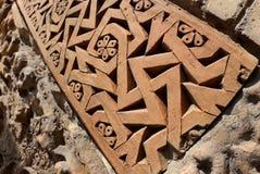 Traditional geometrical muslim ornaments with fertility swastika symbol on the medieval Karakhanid`s tomb in Uzgen,Osh Region, Kyr stock photo