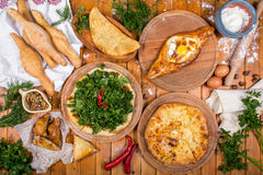 Traditional Georgian adjara khachapuri and Kolkh khachapuri on the table. Homemade baking. Top view. Flat lay.  Stock Photos