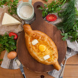 Traditional Georgian adjara khachapuri on the table. Homemade baking. Top view. Flat lay.  Stock Photos