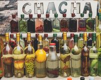traditional georgian alcohol drink chacha in bottles with different fruits and herbs selling royalty free stock images