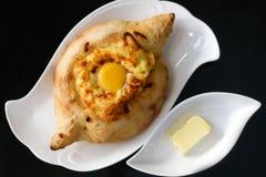 Adjarian khachapuri with eggs on the table. Royalty Free Stock Photos