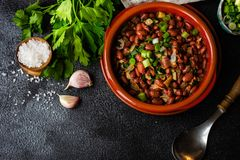 Traditional georgian dish lobio. Traditional georgian red beans dish lobio with pomegranate on rustic table with copy space stock image