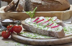 Traditional German Bread. Traditional crusty German Bread with cream cheese and radishes on a wooden plate Royalty Free Stock Images