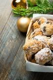 Traditional German Christmas pastry mini stollen in wicker basket on plank wood table. Fresh green juniper branch golden ornament. Balls. Rustic vintage style stock photo