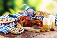 Traditional German cuisine, Schweinshaxe roasted ham hock. Beer, pretzels and various Bavarian specialties. Oktoberfest background. Traditional German cuisine stock image