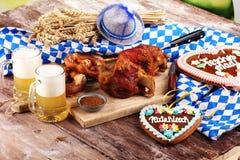 Traditional German cuisine, Schweinshaxe roasted ham hock. Beer, pretzels and various Bavarian specialties. Oktoberfest background. Traditional German cuisine stock images