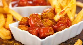 Traditional German currywurst, served with pommes on wooden background. royalty free stock photo