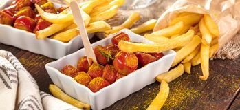 Traditional German currywurst, served with pommes on wooden background. stock photography