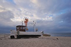 Traditional german fishing boat on the beach of Baltic sea in the sunset before storm. Stock Image