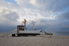 Traditional german fishing boat on the beach of Baltic sea in the sunset before storm. Picture taken in East Germany Stock Photography