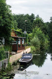 Traditional german house near the channel. Traditional german house near the channel with a garden a a boat under the old high trees Stock Photography