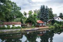 Traditional german house near the channel. Traditional german house near the channel with a garden a a boat under the old high trees Royalty Free Stock Photography
