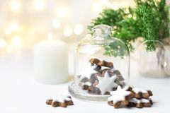 Traditional German star shaped cinnamon cookies with icing in cloche dome bell glass jar on white table. Lit candle juniper lights royalty free stock photography
