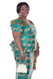 Traditional Ghana. Senior African woman with traditional Ghana clothing, green dress and white handbag Royalty Free Stock Photos