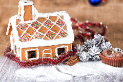 Traditional gingerbread house. On a background of Christmas decorations Royalty Free Stock Photography