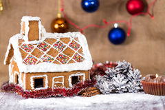 Traditional gingerbread house. On a background of Christmas decorations Royalty Free Stock Images
