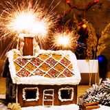 Traditional gingerbread house. On a background of Christmas decorations with fireworks Stock Photography