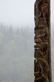 Traditional Gitxsan totem pole with mist covered forest behind Stock Photography