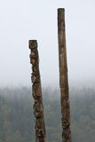 Traditional Gitxsan totem poles with misty forest behind Royalty Free Stock Image