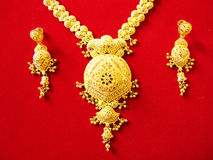 Traditional gold necklace. A beautifully carved golden necklace with earrings Royalty Free Stock Photo