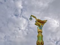 Traditional Golden Bird Lighting Pillar Against Cloudy Sky. Low Angle View of Traditional Golden Bird Lighting Pillar Against Cloudy Sky royalty free stock photography