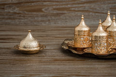 Traditional Golden Coffee Cup Set in a Tray on Wooden Background Royalty Free Stock Photography