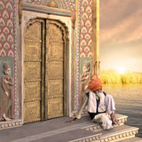 Traditional golden door. Old man near a traditional indian door in the sunrise Royalty Free Stock Photography