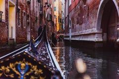 Traditional gondola on narrow canal in Venice, Italy stock photography