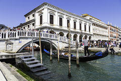 Traditional gondolier rowing through the channels. Gondola trip Stock Photography