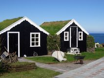 Traditional grass-roof houses in Iceland. Traditional black grass-roof country houses at the sea shore in the Northern part of Iceland Royalty Free Stock Image