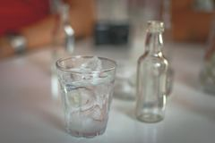 Traditional Greek alcohol drink - Tsipouro. Glass of spirit drink standing ontable with a small bottle royalty free stock images