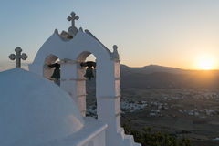 Traditional Greek beauty with a church against the sun on top of a mountain. Stock Photos