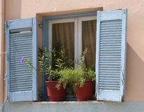 Traditional Greek Blue Window Shutters and flowers Stock Image