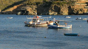 The traditional Greek boats for fishing near beach at sunset. Crete, Greece stock video footage