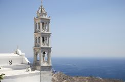 Traditional greek church bell tower and the Aegean sea in Tinos, Greece Stock Photos