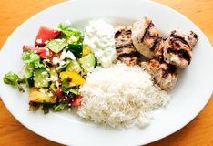 Traditional greek dinner with lamb kabobs, salad, rice and tzatz Stock Image